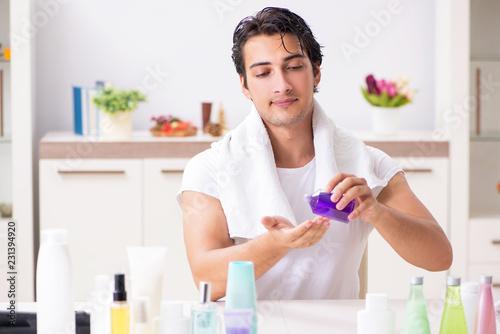 Leinwanddruck Bild Young handsome man in the bathroom in hygiene concept