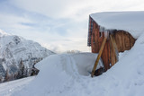 Wooden barn under snow on a mountain side - 231397932