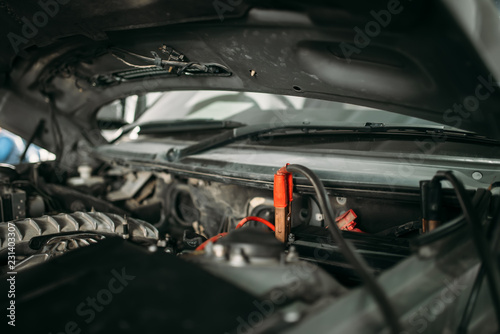 Car with opened hood, wire for battery recharging - 231403307