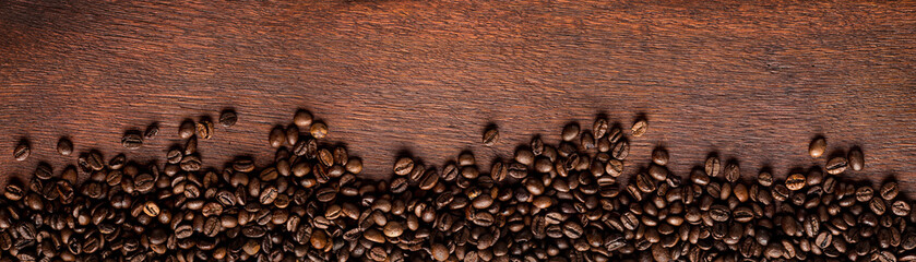 fresh roasted coffee beans on natural dark oak wood panorama background