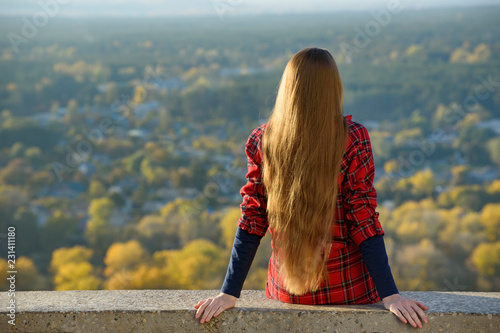 Young woman with long hair sits on a hill overlooking the city. Back view