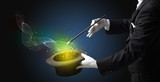 Illusionist hand starts to conjure with white glove and magic wand - 231414332