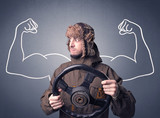 Young man holding black steering wheel with muscly arms drawn next to him - 231415108