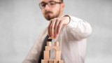 Young handsome businessman using wooden building blocks  - 231418729