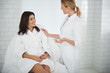 Leinwanddruck Bild - Portrait of pretty woman in soft bathrobe lying on daybed while beautician in white lab coat touching her shoulder. Ladies looking at each other and smiling