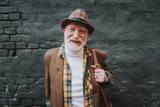 Waist up portrait of joyful hipster pensioner posing near black wall outdoor and happy smiling - 231429754