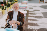 Waist up portrait of stylish old man sitting in outdoor cafe and looking firmly in front of him. Copy space on right side - 231430118