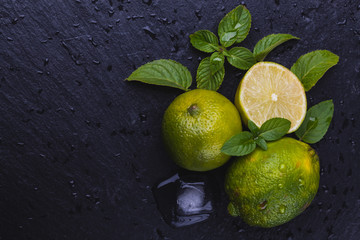 Fresh ripe limes with mint on black slate stone background.
