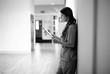 Leinwanddruck Bild - Nurse reading through medical records in the hallway