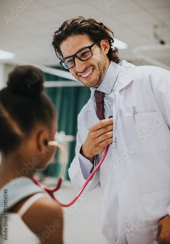 Leinwanddruck Bild Friendly pediatrician entertaining his patient