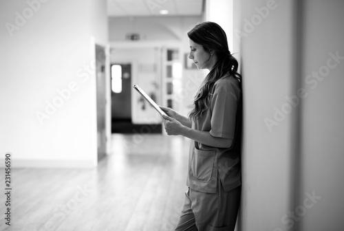 Leinwanddruck Bild Nurse reading through medical records in the hallway