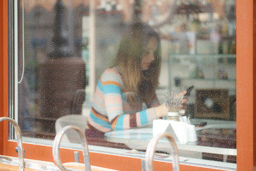 Defocused photo through the window of a girl in caffe with mobile phone
