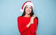 Beautiful happy young cheerful woman in red and santa hat posing on pastel blue background