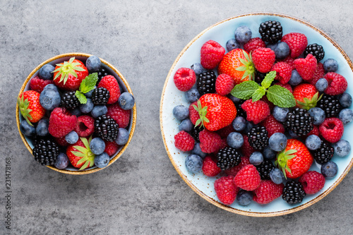 Fresh berry salad on blue dishes. Vintage wooden background. - 231478168