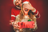 Happy boyfriend covering surprised girlfriend eyes while she's opening christmas present - 231484337