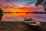 boats by the wooden bridge over the lake during a beautiful sunset - 231511984