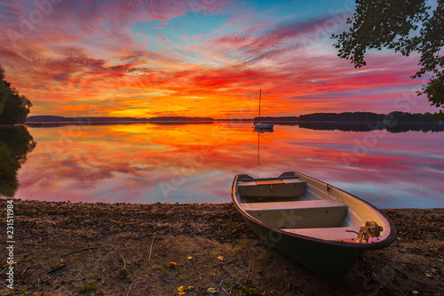boats by the wooden bridge over the lake during a beautiful sunset