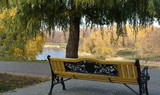 Bench under a willow tree on the embankment of Tambov, Russia and a view of the Tsna River