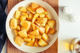 Top view on roasted potato in a white pan on a kitchen table. Modern style, vegetarian food. - 231553948
