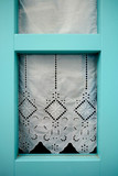 Wooden window with lace curtain