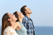 Leinwanddruck Bild - Profile of three friends breathing fresh air on the beach