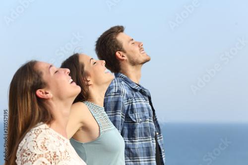 Leinwanddruck Bild Profile of three friends breathing fresh air on the beach