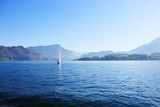 Yacht under white sail on lake surrounded by ridge of mountains on clear sunny day. - 231558515