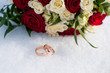 Wedding rings and colorful bouquet on the snow