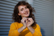 Quadro Lifestyle portrait: cheerful brunette model with curly hair in yellow sweater showing heart sign