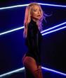 Fashion art photo of elegant model in seductive black swimsuit with light neon colored club spotlights