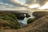 Rock arch and the rugged Pacific at sunset with dramatic clouds - 231580303