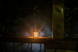 Retro style lantern at night. Beautiful colorful illuminated lamp at the balcony in the garden. Selective focus - 231585534