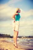 Blonde woman wearing dress playing jumping on beach - 231588593