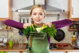 Woman in kitchen having vegetables holding shopping basket - 231589145
