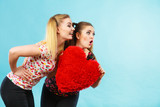 Happy two women holding heart shaped pillow - 231589350