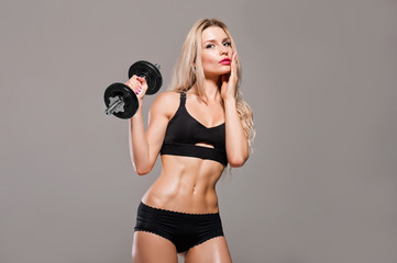 Beautiful athlete posing with a dumbbell in the studio. © andy_gin