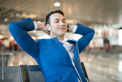 Man listening to music while waiting in an airport - 231595722