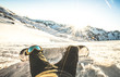 Snowboarder sitting at sunset on relax moment in european alps ski resort - Winter sport concept with guy and snowboard on mountain top ready to ride - Legs point of view on vintage contrast filter