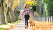 Woman walking golden retriever dog in Fall leaves