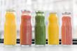 Leinwandbild Motiv Kiwi juice. Nice yummy kiwi juice standing in the middle of different fruit juices near the window in cafeteria