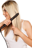 smiling young woman ironing her hair with hair iron on white backgrund