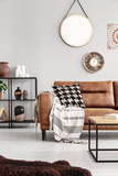 Vertical view of warm ethno living room with leather couch with patterned pillow and mirror and clock on beige wall, real photo - 231639757
