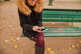 Girl using cellphone in park with autumn colors. - 231655102