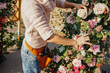 Leinwanddruck Bild - Woman florist with shears in her hands near the arch with autumn flowers, works.