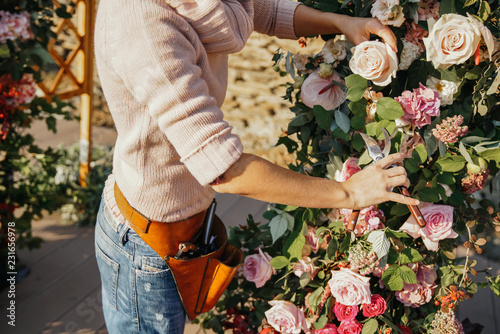 Leinwanddruck Bild Woman florist with shears in her hands near the arch with autumn flowers, works.