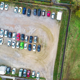Vertical aerial photo of a gravel parking lot with rows of parked cars. - 231657589