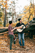adult woman and man having fun with guitar on autumal background