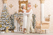 Portrait of a cute happy olderly couple dancing near christmas tree - 231663794