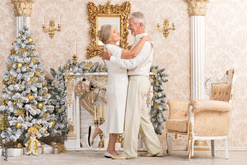 Portrait of a cute happy olderly couple dancing near christmas tree © aletia2011