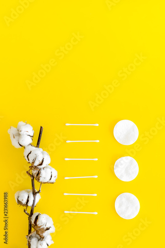 Leinwanddruck Bild Products made of cotton. Bath accessories. Towels, cotton pads and swabs near dry cotton flowers on yellow background top view pattern copy space